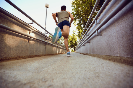 A male runner runs along the road to the park in the summer.
