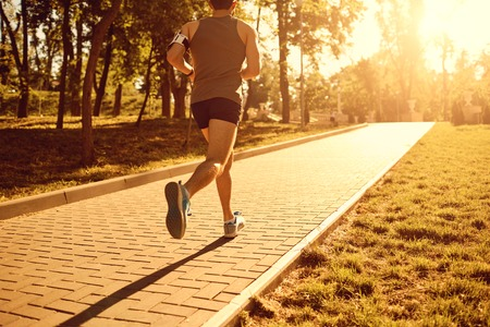 A male runner is running down the road in the park at sunset.
