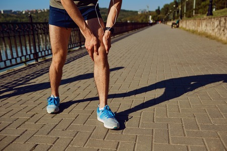 Injury, stretching, bruise on a run in a runner. Stock Photo