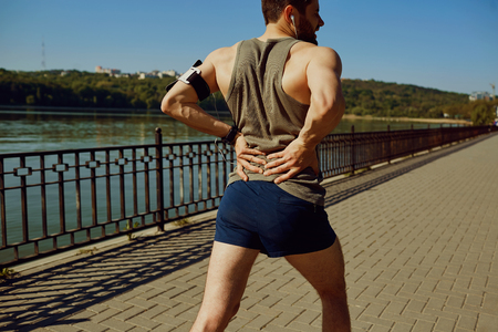 Injury, sprain contusion of the back jogging runners. Stock Photo