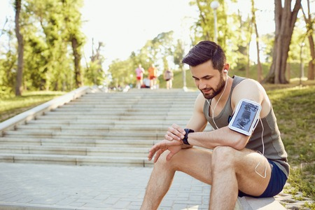 A male runner looks at a smart watch on his arm. Stock Photo