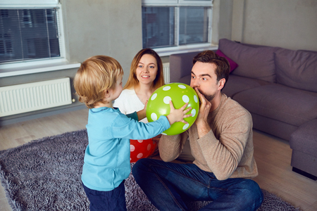 A happy family with an air balloon is playing with the child in the room.