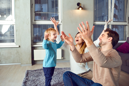 A happy family plays with a child indoors. Stock Photo