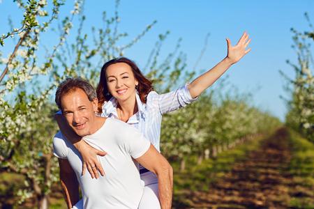 Una bella coppia positiva sta camminando nel parco in estate. Archivio Fotografico