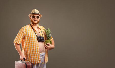 Een grappige dikke bebaarde toerist met een ananas en een koffer glimlacht tegen de achtergrond voor de tekst. Stockfoto