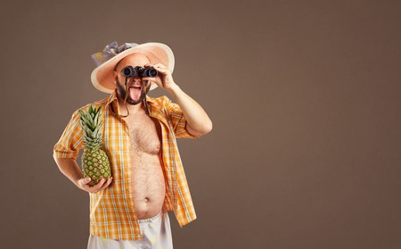 Thick funny man with a beard in a hat with binoculars looking at the background for text.