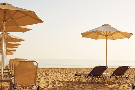 Beach in the resort in the summer. Umbrellas and chaise lounges on the sand of the summer beach.