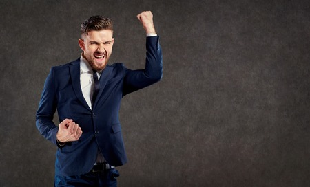 A young businessman with a beard enjoys a success on a gray background. Stock Photo