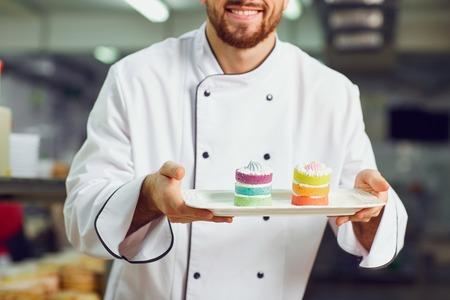 Ein Konditor mit Dessert in den Händen in der Bäckerei.