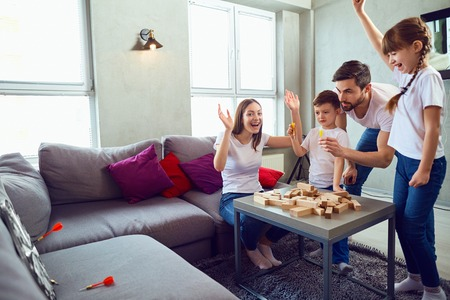 Happy family playing board games at home. Mother, father and children play together. Standard-Bild - 107723023