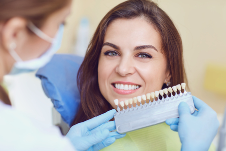 Teeth whitening dental clinic. Closeup of a young woman with beautiful smile at the dentist.