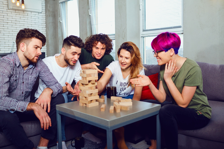 A cheerful group of friends play board games in the room. Stock Photo