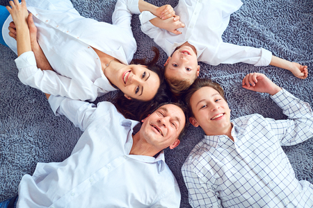 Happy family smiling lying on the floor. View from above. Stock Photo