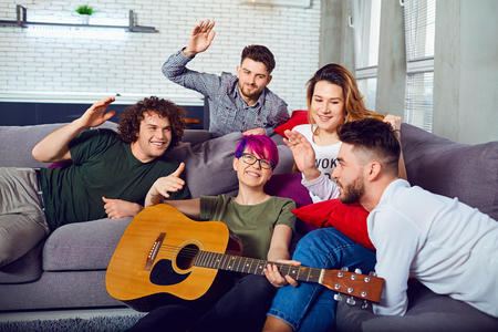 Cheerful group of friends with a guitar at a party in a room.