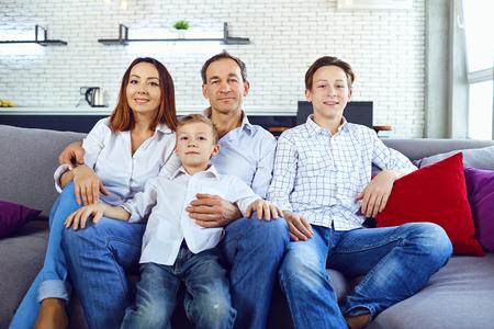 Happy family smiling sitting on sofa in room. Happy family. Stock Photo