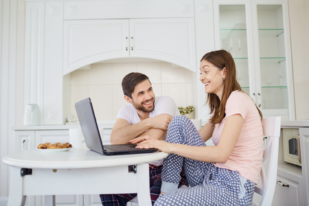A young couple is having breakfast at the table, working with a laptop in the morning in the kitchen.