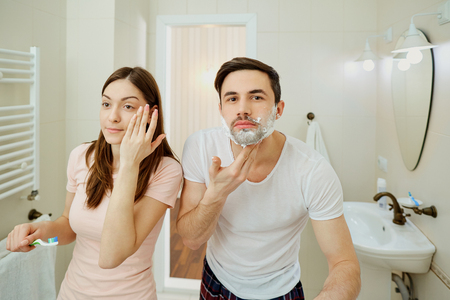 Couple in the morning personal hygiene in the bathroom.