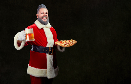 Santa with pizza and a glass of beer in his hands at Christmas on a background of copyspase.