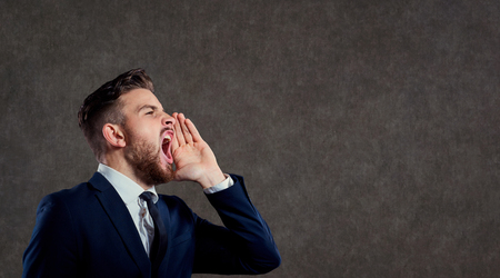 Young businessman with a beard screaming against a gray background. Stock Photo
