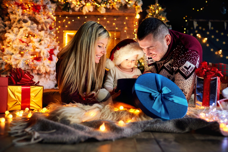 Happy family with a baby in a Santa Claus hat in a Christmas room in Christmas day. Stock Photo