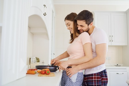 Young couple preparing food in the kitchen in the morning.