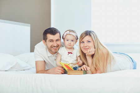 Happy family lying on bed in bedroom. Stock Photo