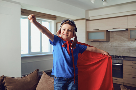 The boy in the costume of a superhero at the window. Stock Photo