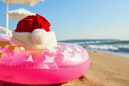 Santa Claus hat on the beach by the sea. Christmas on vacation by the sea. Concept of Christmas in a summer resort.