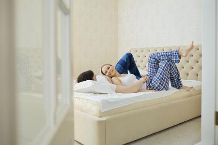 Couple in bed hugging in bedroom. Relations between men and women.