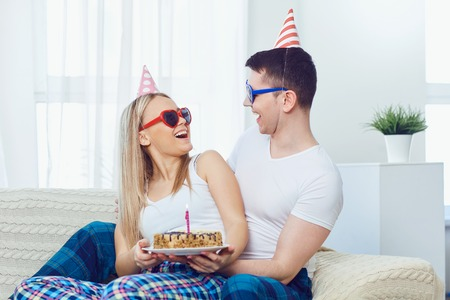 Couple with a cake with candles congratulates on his birthday on the background of the window in the room.