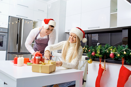 A couple in Santas caps wrapping presents in a room on Christmas Day. Stock Photo