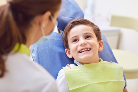 A child with a dentist in a dental office. Dental treatment in a childrens clinic.