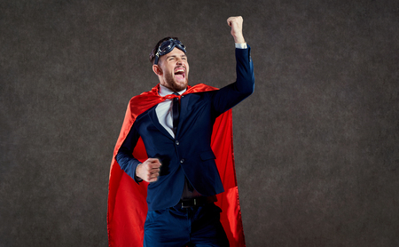 A businessman in a superhero costume is a winner. The concept of success victory.