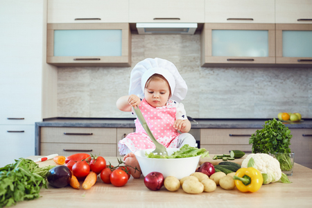 A little girl in a chefs hat prepares food in the kitchen.