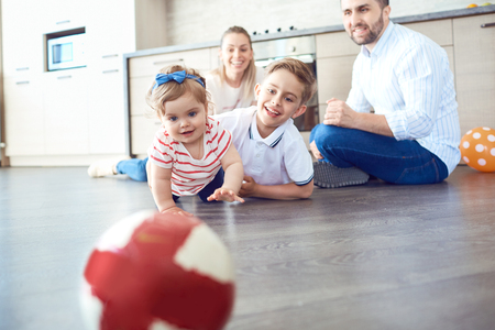The family plays fun on the floor indoors.