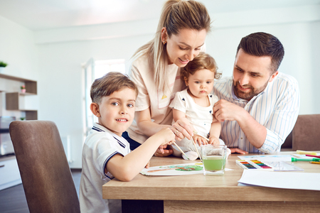 Happy family draws paints on a paper at the table in the room.