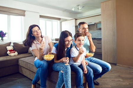 Happy family having fun watching TV sitting on sofa.