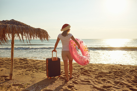 A girl in a Santa Claus hat with a suitcase on the beach on Christmas Day. The concept of Christmas by the sea.