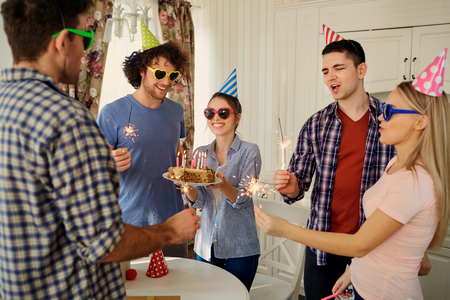 Friends with cake celebrating birthday at a party in room. Stock Photo