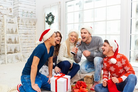 A group of friends in Santas hats are playing the guitar and singing at home on Christmas Day.