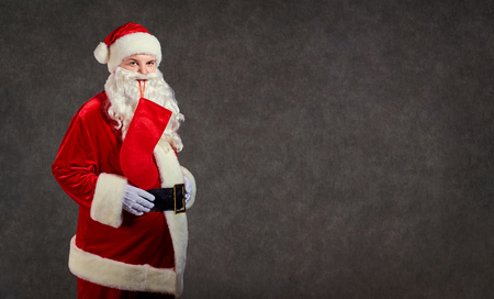 Happy funny Santa Claus with red sock on gray background. Stock Photo