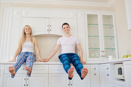 Funny young couple in the morning embrace in the kitchen.