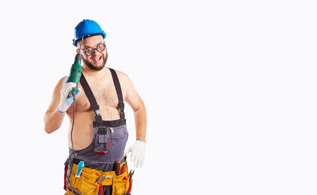 The fat funny man builder with a drill on a background for text. Stock Photo