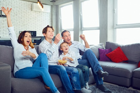 Happy family having fun watching TV sitting in the room. Stock Photo