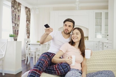 A girl and a guy with a remote control watch TV sitting on the sofa in the room.