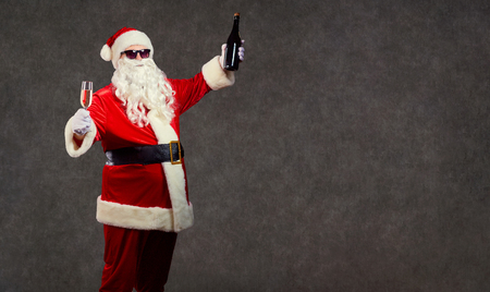 Santa Claus with a glass of champagne on the background for text.