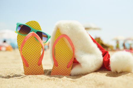 Santas hat on the beachon Christmas Day.  The concept of celebrating Christmas in a seaside resort.