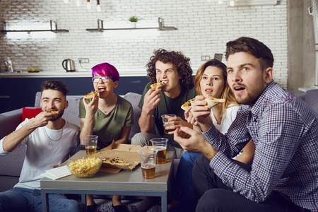 A group of friends eating pizza while sitting on the couch in the room.
