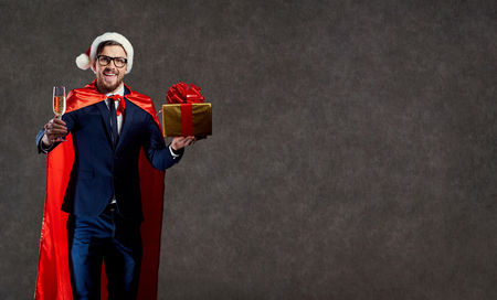 Businessman in a Santa Claus costume, a superhero with a glass of champagne and a gift congratulates Merry Christmas on a background for the text.