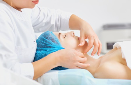 Beautician makes facial massage to a young woman in the spa salon. Stock Photo